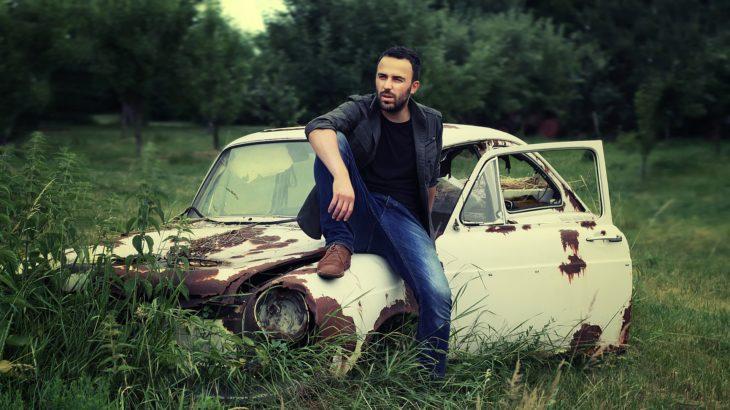 古い車に腰掛けている男の人の写真